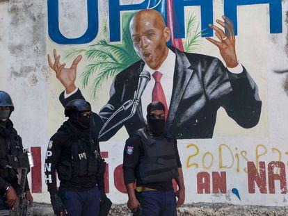 Varios policías frente a un mural del presidente de Haití, asesinado esta semana.
