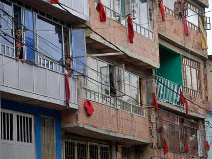 Residentes de un barrio en el sur de Bogotá despliegan trapos rojos en sus ventanas, una señal de alerta para pedir ayuda estatal.