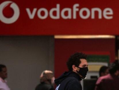 Un hombre camina ante un cartel de Vodafone.