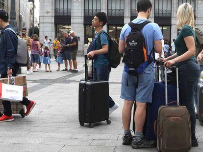 Turistas con maletas en la Puerta del Sol de Madrid.