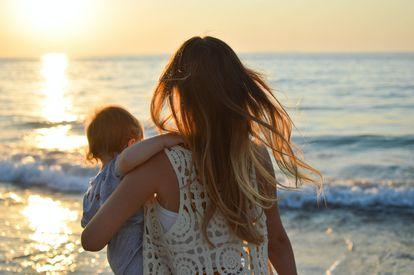 Una madre abraza a su hijo frente al mar.
