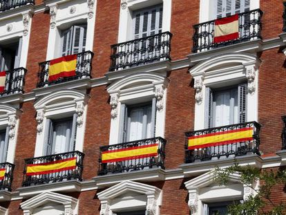 Varias banderas cuelgan de los balcones de un edificio en Madrid.