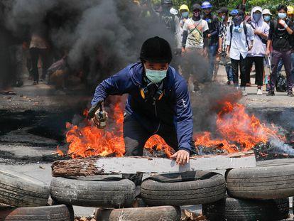 Un manifestante tras una barricada formada en las protestas en Yangon (Myanmar), este sábado.