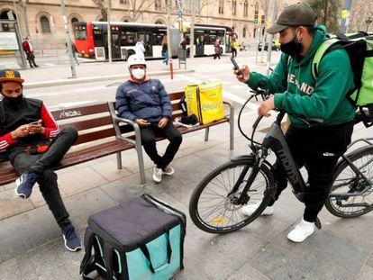 Repartidores de Glovo, Deliveroo y Uber Eats esperando algún servicio en Barcelona.