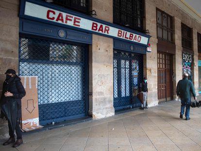 Varias personas pasan por delante de un café cerrado en la plaza Nueva de Bilbao, el pasado vienes.