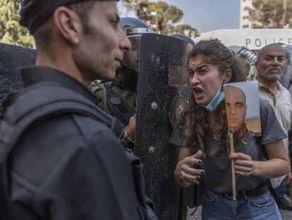 La policía cierra el paso a una palestina que protesta con una foto de NIzar Banat, el jueves en Ramala.