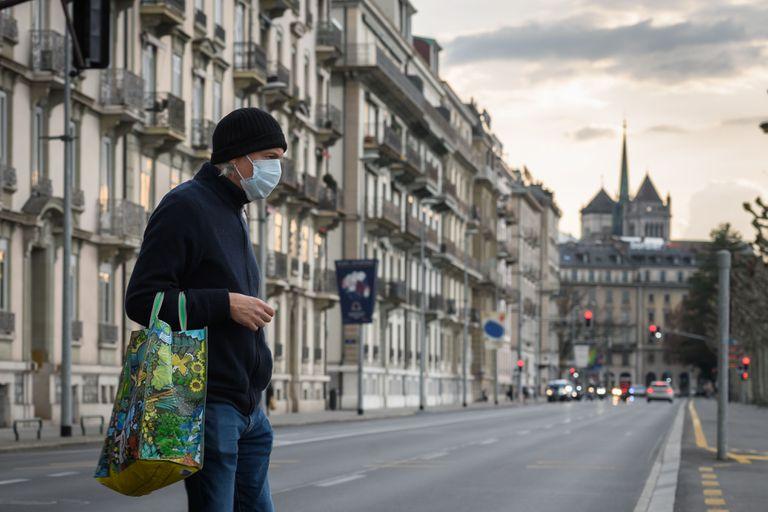 Un hombre con mascarilla cruza la calle en Ginebra, este viernes, cuando el Gobierno suizo endureció aún más las medidas contra el coronavirus.