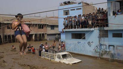 Una mujer es trasladada en un arnés a causa de las inundaciones en Lima, Perú.