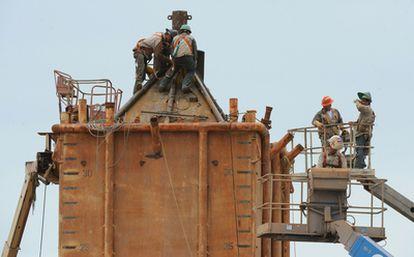 Trabajadores de BP trabaja en el montaje de una cúpula que pretenden instalar encima del pozo para facilitar la extracción del crudo.