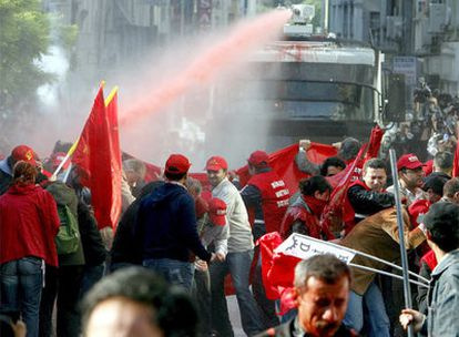 Un grupo de manifestantes se resguardan del chorro de agua a presión disparado desde una tanqueta de la policía, en la manifestación del Primero de Mayo en Estambul.