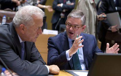 El comisario europeo para la migración, Dimitris Avramopoulos (izq) conversa con el comisario europeo de seguridad, Julian King, este jueves en Bruselas.