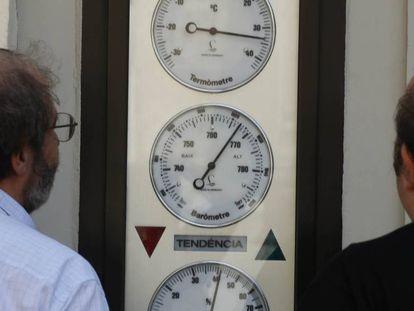 Dos hombres miran un termómetro en la calle