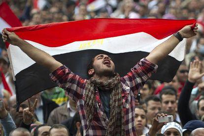 Un joven egipcio muestra la bandera nacional, mientras grita consignas contra el presidente Mubarak, el 11 de febrero de 2011, en la plaza Tahrir de El Cairo.