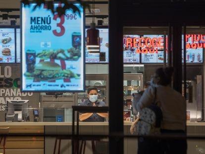 Una clienta se dispone a entrar en un restaurante de Madrid minutos antes del comienzo del estado de alarma.