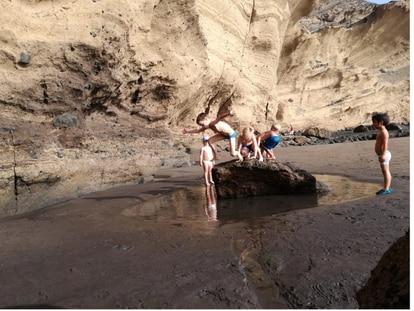 La playa puede ser un espacio de aprendizaje fundamental este verano. En la imagen varios niños, alumnos de la playa escuela El Médano, juegan en los charcos de la playa en un día de escuela.