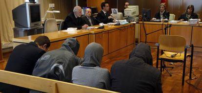 Los cuatro acusados, de espaldas, y el abogado defensor de dos de ellos, segundo por la izquierda.