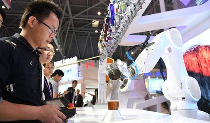 Un robot prepara una bebida en frente de varios espectadores en Chongqing (China), la pasada semana.