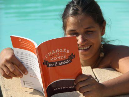 Una joven lee uno de los ejemplares de 'Cambiar el mundo en 2 horas'.