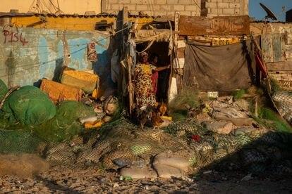 Una mujer alimenta a sus gallinas frente a la casa que se ha construido sobre los restos de viviendas que el mar ha destruido.