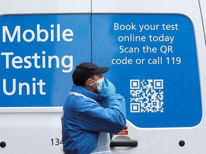 Un sanitario, junto a una unidad móvil para realizar pruebas de covid en Londres.