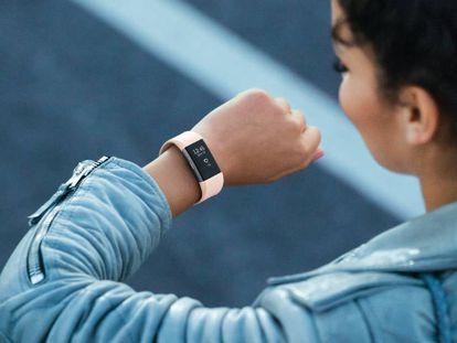 Una usuaria de una pulsera de actividad mira la hora en su Fitbit Charge 2.