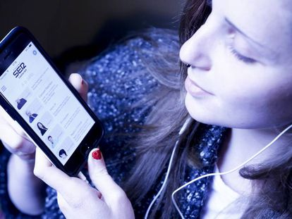 Una usuaria escucha con su móvil un 'podcast' de la Cadena SER.