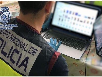 Un policía analiza material informático en una operación contra la pornografía infantil en Madrid.