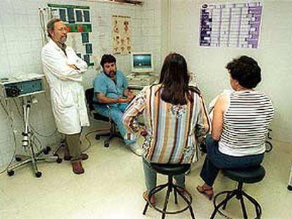 El urólogo Alejandro Galacho (de pie) y el enfermero Francisco Milla, del Clínico de Málaga, con dos pacientes.