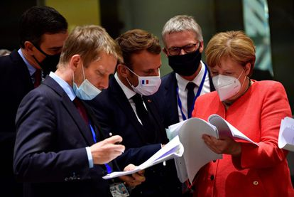 De izquierda a derecha, el presidente del Gobierno español, Pedro Sánchez; el presidente francés, Emmanuel Macron, y la canciller alemana, Angela Merkel, examinan documentos durante la cumbre de la UE en Bruselas el 20 de julio.