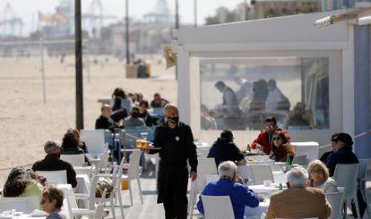 Un camarero atiende las mesas de una terraza en uno de los restaurantes de la playa de la playa de la Malvarrosa de Valencia.