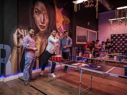 Varios grupos de jóvenes juegan al 'beer pong' en el local de la calle Doctor Fourquet, 20 de Madrid este sábado.