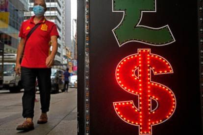 Un hombre pasea junto a una casa de cambios en Hong Kong.