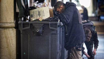 Un hombre busca comida en los contenedores de un restaurante.