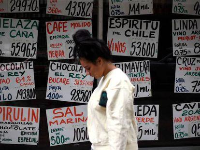 Una mujer anda frente a un escaparate en Caracas (Venezuela).