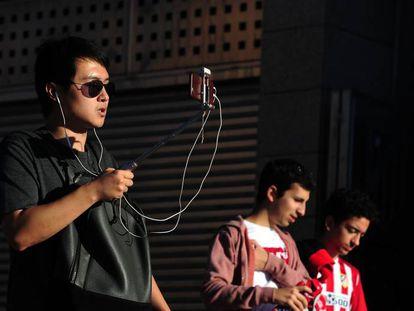 Un aficionado del Atlético de Madrid retransmite en directo con su móvil antes de un partido.