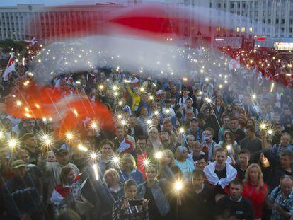 Manifestantes opositores encienden las luces de sus móviles, el miércoles en la plaza de la Independencia de Minsk.