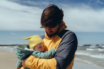 Un padre pasea con su bebé por una playa.
