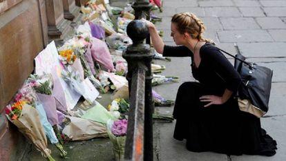 Una mujer deja flores por las víctimas del atentado en el Manchester Arena en mayo.