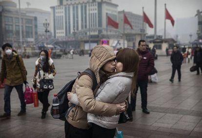 Una pareja se besa antes de entrar en la estación de tren de Pekín (China).