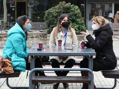 Las candidatas Manuela Bergerot (Más Madrid), Alejandra Jacinto (Unidas Podemos) y Hana Jalloul (PSOE), en un banco de la plaza de Quintana.