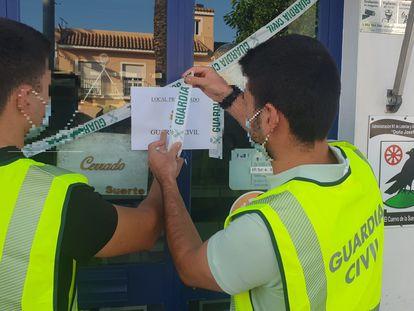 Agentes de la Guardia Civil precintan el establecimiento de lotería en El Cuervo que los Panecito adquirieron para blanquear.