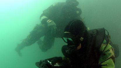 Nadadores de los Navy Seals entrenan en una piscina.
