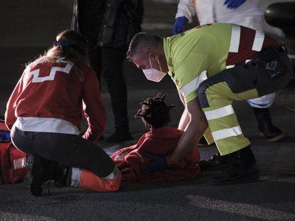 Uno de los niños atendidos por los servicios de emergencia en la noche del martes, sobre el asfalto del muelle de Arguineguín.