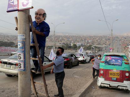 Un hombre con una máscara de Hernando de Soto coloca un cartel antes de una aparición del candidato en Villa El Salvador, Lima, el pasado 5 de abril.