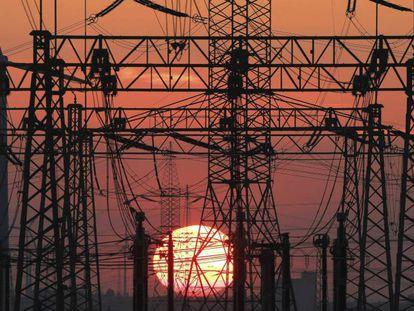 En la imagen, una puesta de sol junto al tendido eléctrico y unos molinos de viento.