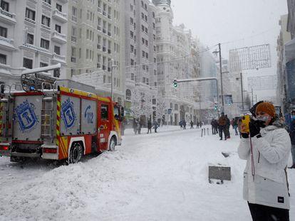 Varias personas pasean por la Gran Via cubierta de nieve en Madrid, este sábado.