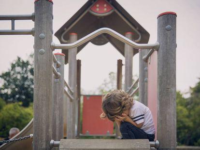Un niño llora en un columpio.