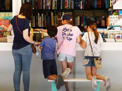 Unos niños libros de un puesto en la 76ª edición de la Feria del Libro de Madrid.