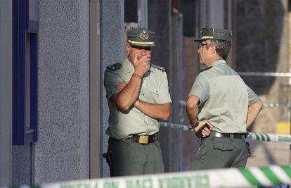 Dos guardias civiles conversan ante la sucursal bancaria de A Cañiza donde uno de sus compañeros ha fallecido esta mañana.