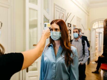 Una empleada mide la temperatura de sus compañeros a la entrada de la oficina.